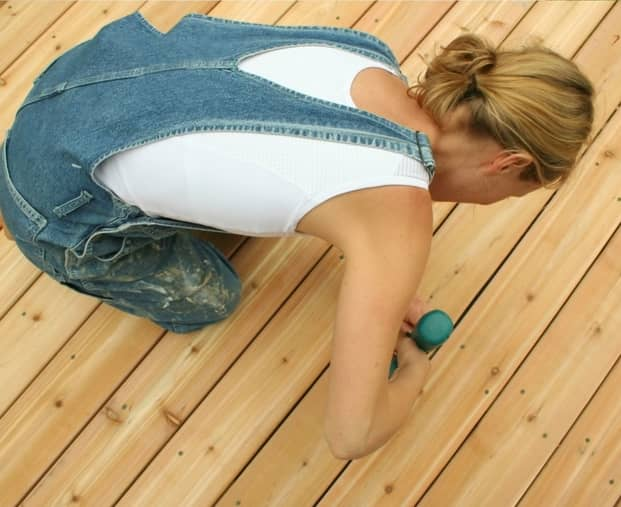 woman laying down boardwalk deck at ipswich decking solutions